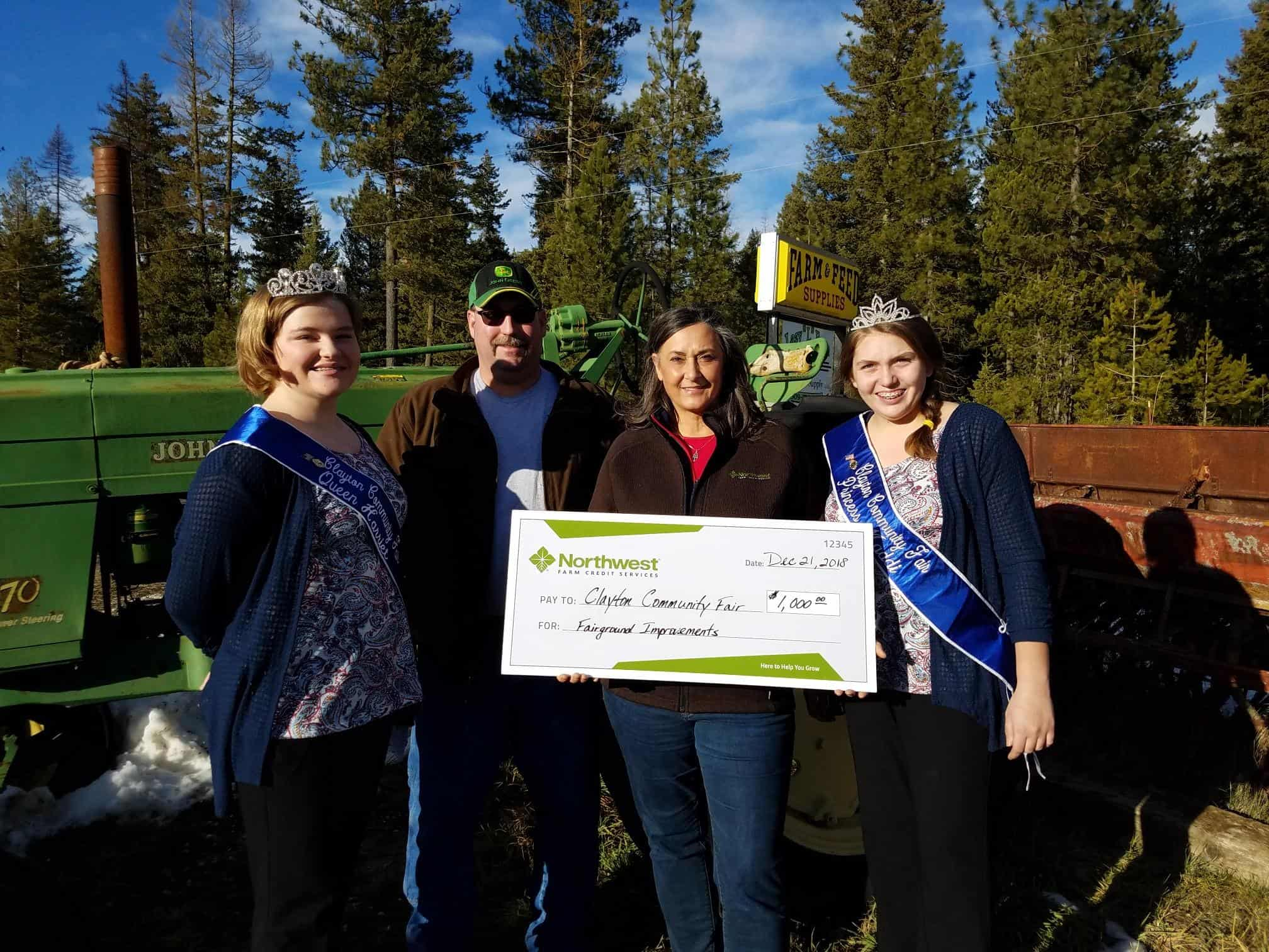 All smiles with the receipt of funds to help improvements are Clayton Community Fair Queen Harriet, Loren Lentz, a Northwest Farm Credit Services representative, and Clayton Community Fair Princess Maddi