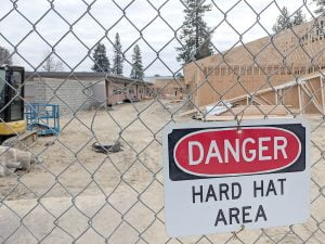 "Fence with sign that reads ""DANGER: Hard Hat Area"" 